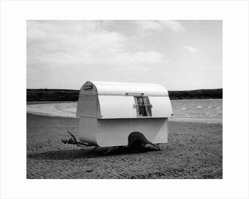 Woman smiling from the window of a trailer caravan on a beach by Anonymous