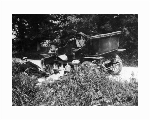 Two men picnicking beside a Vauxhall car by Anonymous