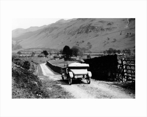 A vintage car travelling along a lane through the Lake District by Anonymous