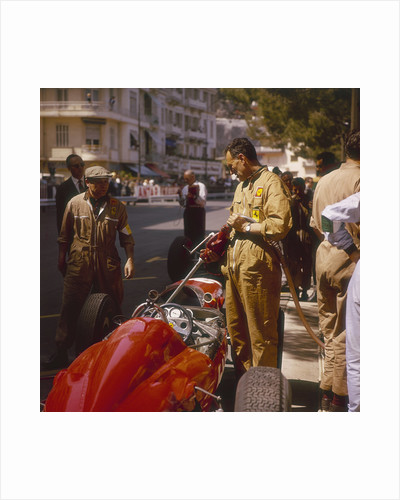 A Ferrari team member filling a car with fuel by Anonymous