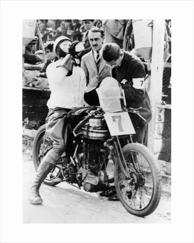 Van Horne taking a drink whilst on his Norton bike by Anonymous