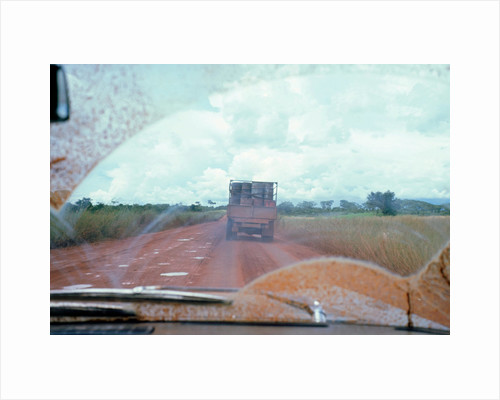 View through muddy windsreen on African dirt road by Unknown