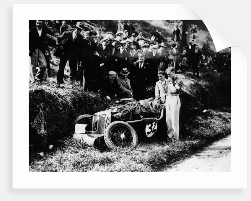 Goldie Gardner by the wreckage of an MG J4 by Anonymous