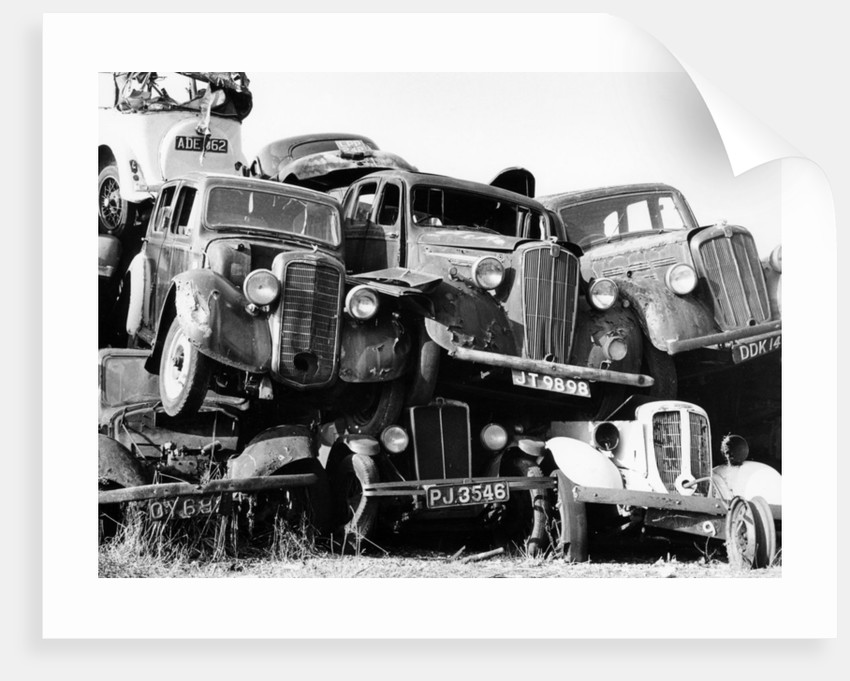 Old cars piled up in a scrapyard, Britain by Unknown