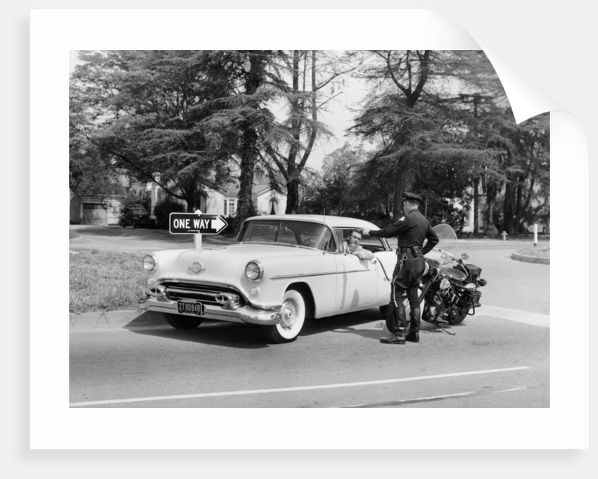 An Oldsmobile at the corner of an American street by Anonymous