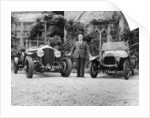 WO Bentley standing between two of his cars by Anonymous