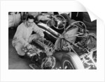 Jack Brabham inspecting the engine of a car by Unknown