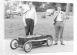 Two men standing by a miniature Sunbeam pedal car by Anonymous