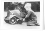 Michael Ware repairing a pedal car by Unknown