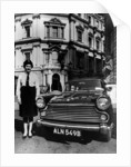 Female chauffeur standing by a 1964 Morris Oxford by Anonymous