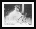 A man at the wheel of his car dressed in a driving coat and goggles by Anonymous