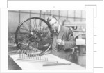 A man in a workshop with a wheel by Unknown