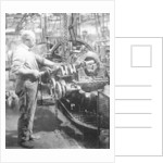 Man operating machinery in a car factory by Unknown