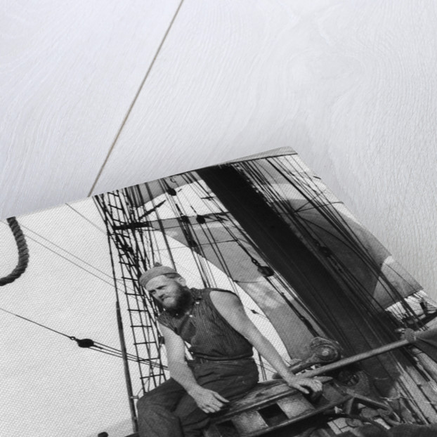 One of the crew on the forecastle head capstan by Alan Villiers