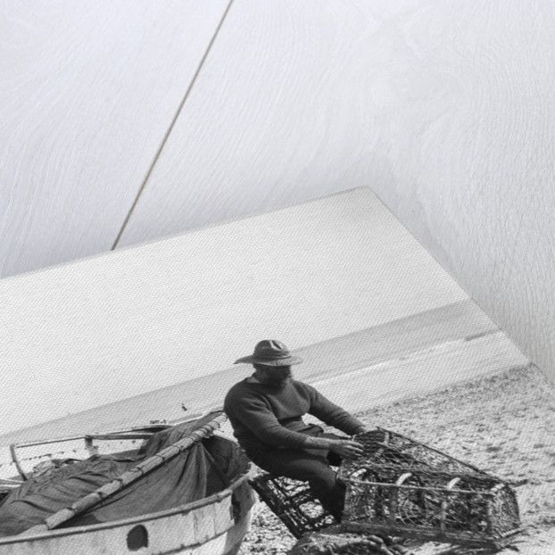 A fisherman in sou'wester mending lobster/crab creels on the beach alongside a beached Sheringham crab boat by Smiths Suitall Ltd.