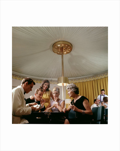 Passengers in smart evening dress, aboard an unspecified cruise liner, enjoy the thrilling distraction of a card game by Marine Photo Service