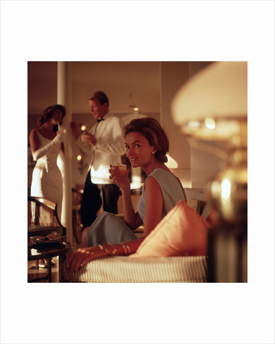A smartly attired female passenger enjoys an evening tipple aboard an unspecified cruise ship by Marine Photo Service