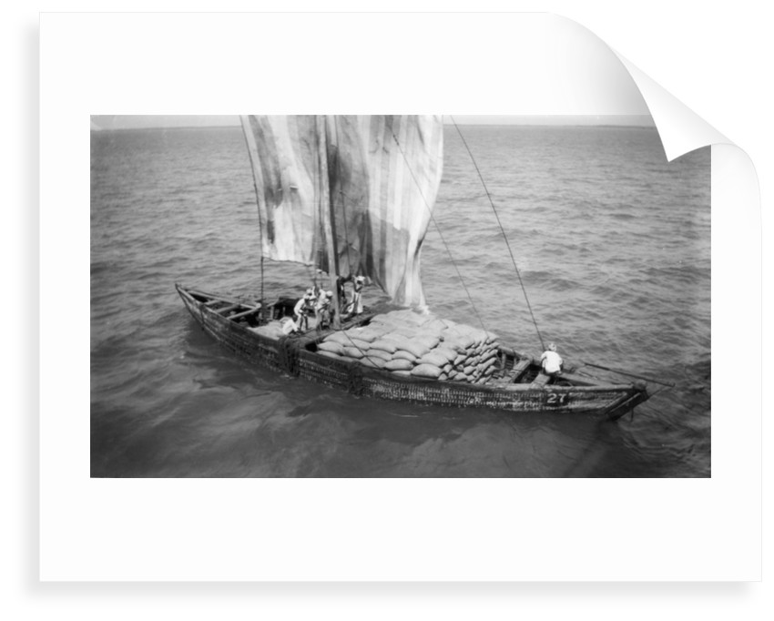 Indigenous boat at sea, laden with sacks by unknown