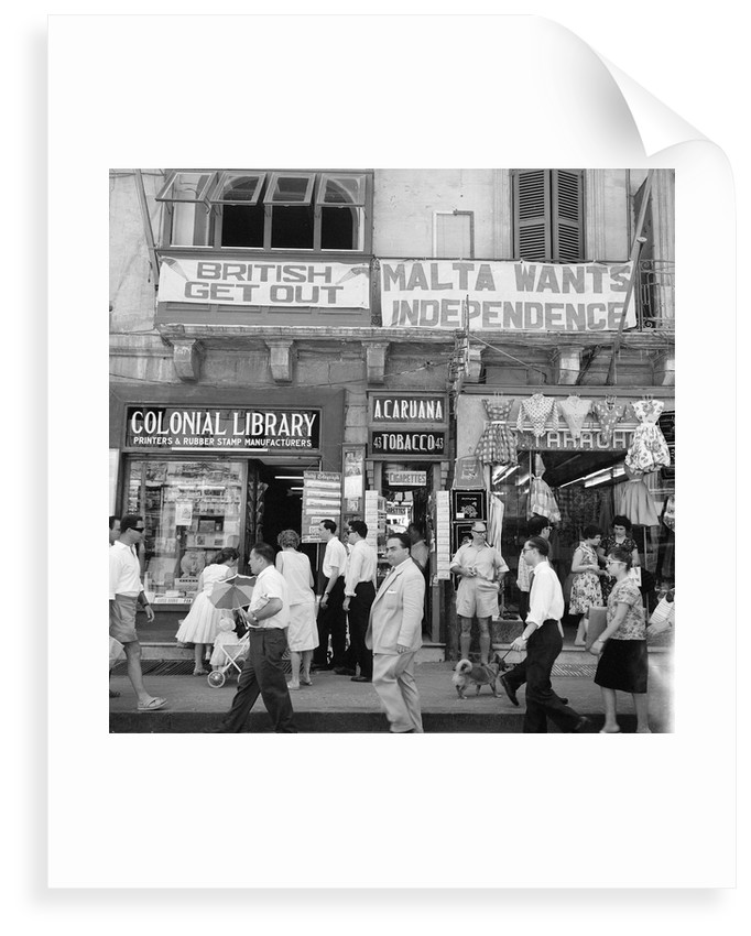 A view of shops with anti-British and pro-Independence signs, possibly on Kings Street, Valetta, Malta. by Marine Photo Service