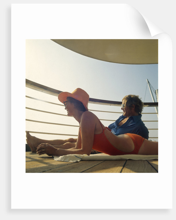 A couple relax and enjoy the sea view on board an unspecificed cruise liner by unknown