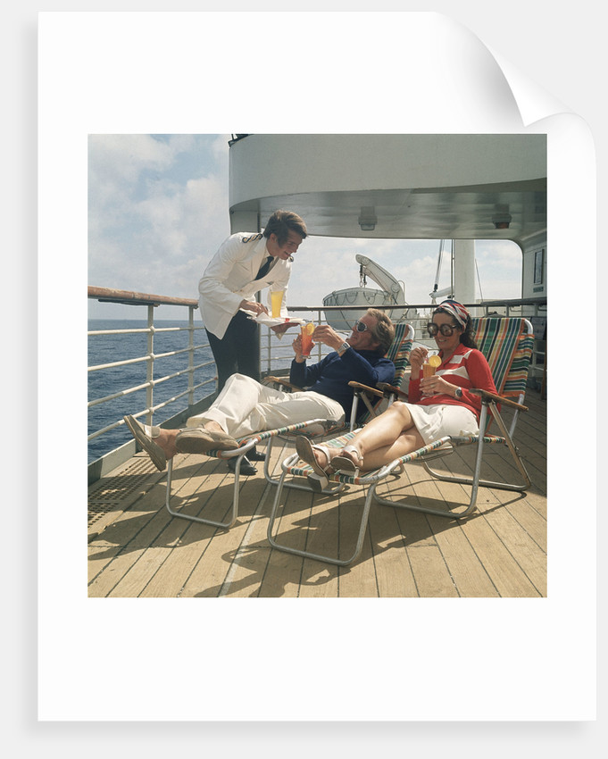 A ship's steward serves drinks to passengers on deck by Marine Photo Service