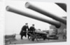 Two ratings pushing a 14-inch shell on a trolley on the battleship 'King George V' (1939). King George V carried about 800 shells for her 10 guns when loaded. by unknown