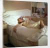 Modern convenience aboard a cruise liner: a female passenger reclines in bed whilst making a phone call; the ship and the conversation's content are unspecified by Marine Photo Service