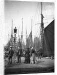 Men and women onlookers at the end of the quay looking at the forest of masts and sails in the harbour at Lowestoft, Suffolk by Smiths Suitall Ltd.