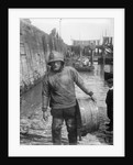 A Folkestone fisherman in smock and sou'wester carrying a tub for fish on the slipway by unknown