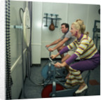 After all the lunches and cocktail evenings, a little exercise is just the thing: two passengers use exercise bikes in the gym of an unspecified cruise liner by Marine Photo Service