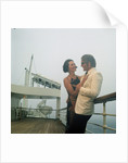 A misty evening offers amorous opportunities on deck for a romantic, smartly dressed, couple on a cruise ship by Marine Photo Service