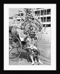 A local rickshaw driver in 'traditional' costume, with a Union-Castle Line ship in the background, at Durban, South Africa by Marine Photo Service