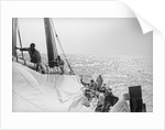 The mainsail down at sea, being prepared by Alan Villiers