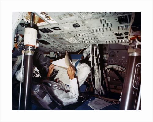 An astronaut inside a NASA Command Module by NASA