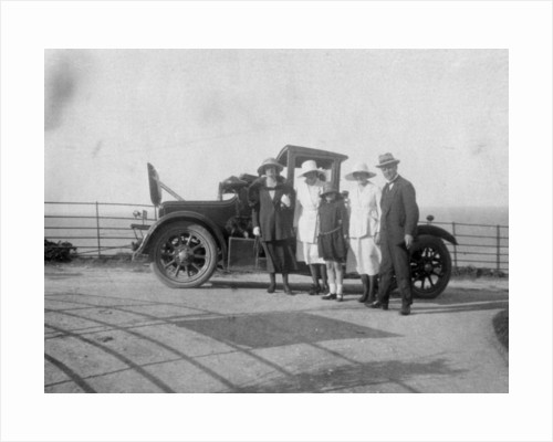 A group of people in front of their car at the seaside by Anonymous