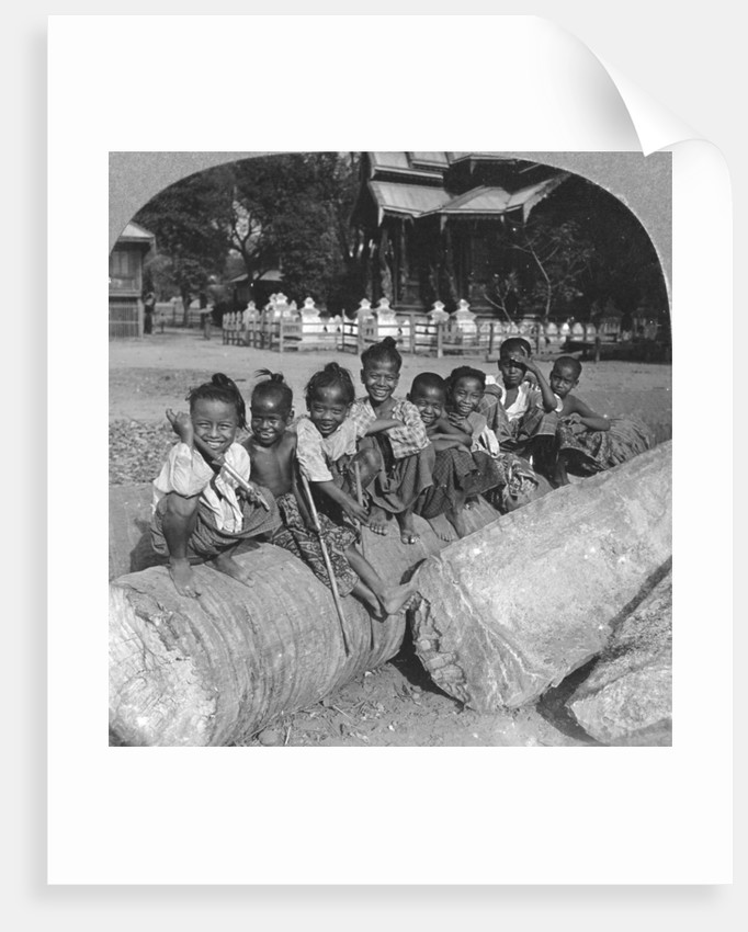 Burmese children sitting on a palm log, Burma by Stereo Travel Co