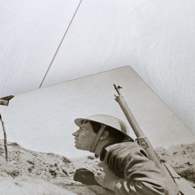 A sentry in the trenches looking through an improvised persicope by Anonymous