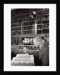 A labourer reads a book in a library by Anonymous