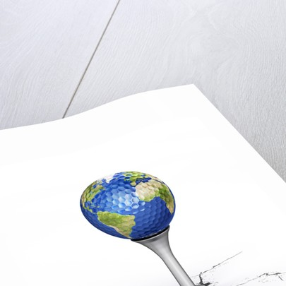 Golf ball with the texture of planet Earth placed on a tee. by Leonello Calvetti